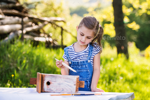 A small girl with a paintbrush outside, painting a wooden birdhouse. - Stock Photo - Images