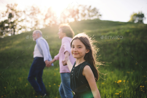 Senior couple with granddaughter outside in spring nature, walking. - Stock Photo - Images
