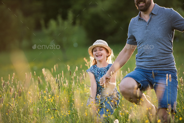 Father with a small daughter running in spring nature. - Stock Photo - Images