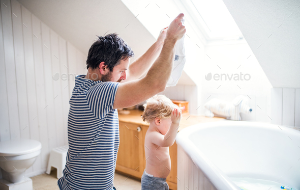 Father with a toddler boy at home, getting ready for a bath. - Stock Photo - Images
