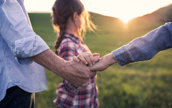 A small girl with her senior grandparents holding hands outside in nature at sunset. - Stock Photo - Images