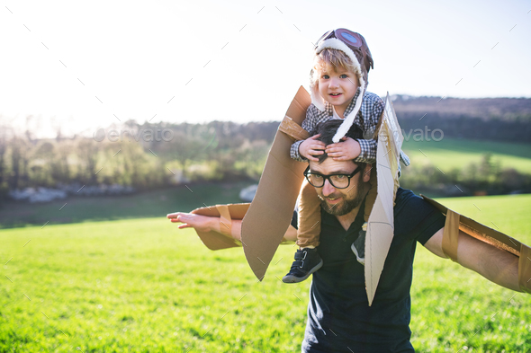 Happy toddler boy and father playing with wings outside in spring nature. - Stock Photo - Images