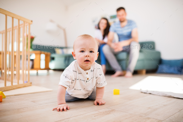 A baby boy crawling on the floor at home, parents in the background. - Stock Photo - Images