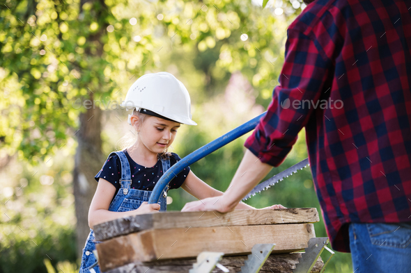 Father with a small daughter outside, making wooden birdhouse. - Stock Photo - Images