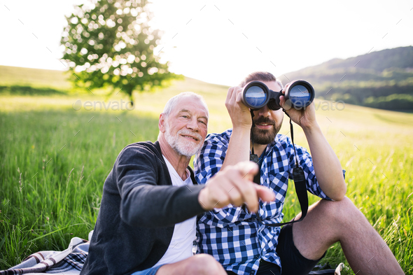 An adult hipster son with binoculars and senior father sitting on the grass in sunny nature. - Stock Photo - Images