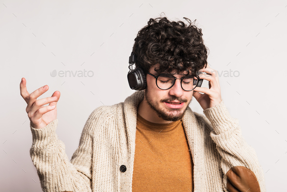 Portrait of a young man with headphones in a studio. - Stock Photo - Images