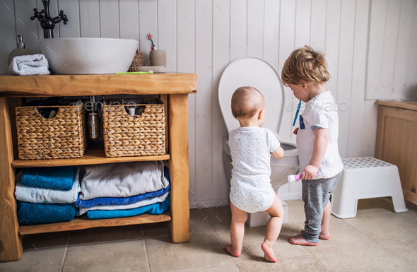 Two toddler children with toothbrush standing by the toilet in the bathroom at home. - Stock Photo - Images