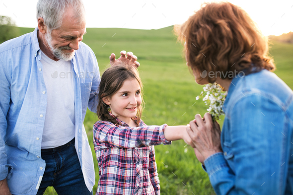 A small girl with her senior grandparents having fun outside in nature at sunset. - Stock Photo - Images