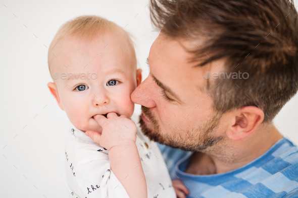 Portrait of a young father with a baby son at home. Close up. - Stock Photo - Images