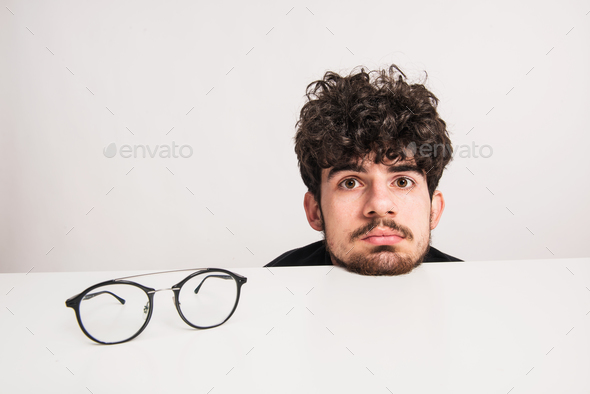 Head of a young man and the eyeglasses in a studio. - Stock Photo - Images