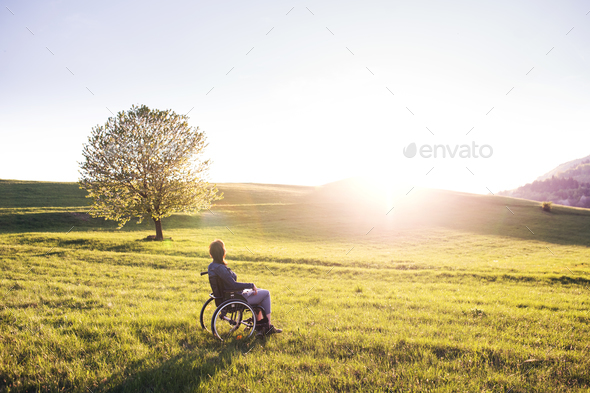 A woman in wheelchair in nature at sunset. - Stock Photo - Images