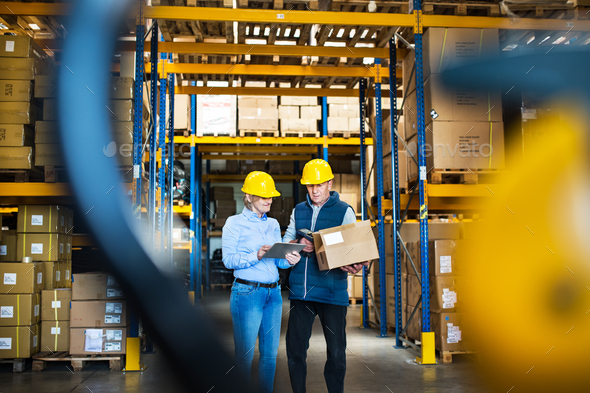 Senior managers or supervisors with tablet working in a warehouse, controlling stock. - Stock Photo - Images