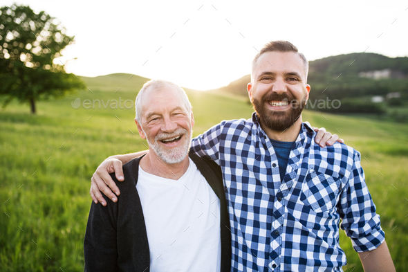 A portrait of an adult hipster son with senior father in nature at sunset, arms around each other. - Stock Photo - Images