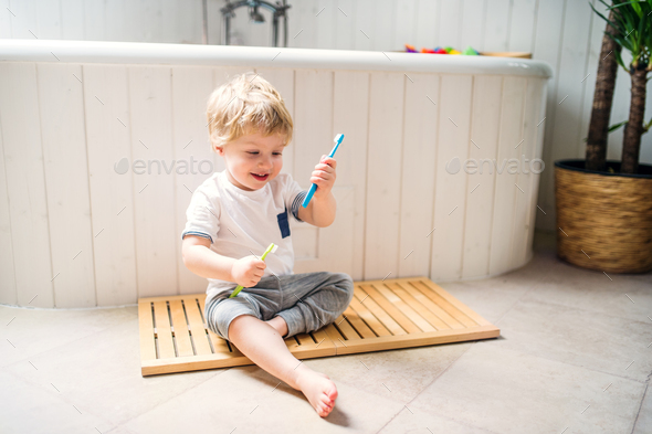 A toddler boy with a toothbrush sitting on the floor in the bathroom at home. - Stock Photo - Images
