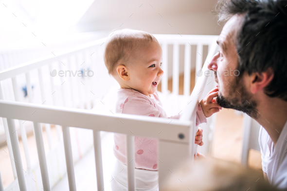 A small toddler girl standing in cot with her father at home. - Stock Photo - Images