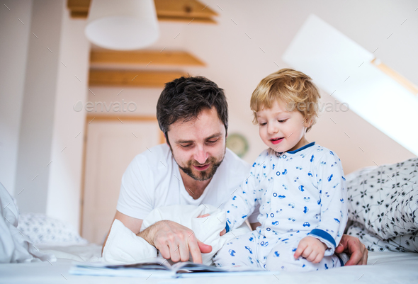 Father with toddler boy reading a book on bed at home at bedtime. - Stock Photo - Images