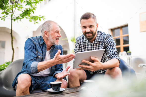 An adult hipster son with tablet and senior father in a cafe in town. - Stock Photo - Images