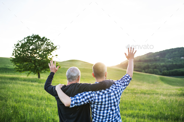 An adult hipster son with senior father on a walk in nature at sunset, arms around each other. - Stock Photo - Images