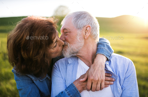 Senior couple outside in spring nature, kissing. - Stock Photo - Images