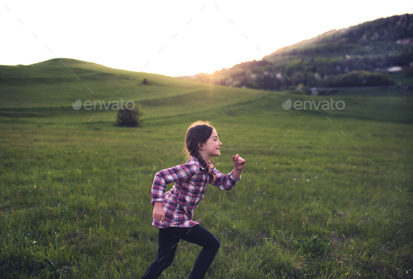 A small girl running outside in nature at sunset. - Stock Photo - Images