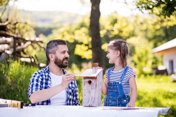 Father with a small daughter outside, painting wooden birdhouse. - Stock Photo - Images