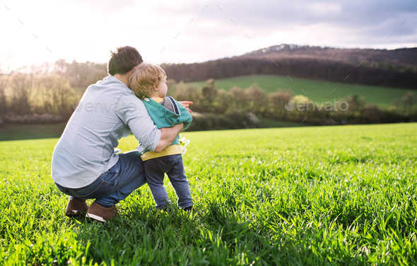 A father with his toddler son outside in spring nature. Copy space. - Stock Photo - Images