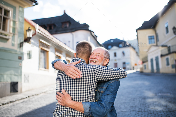 An adult hipster son and his senior father in town, hugging. - Stock Photo - Images