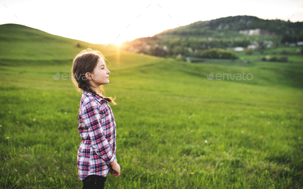 A small girl standing outside in nature. - Stock Photo - Images