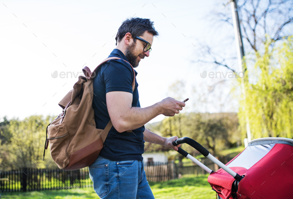 A father with smartphone and jogging stroller on a walk outside in spring nature. - Stock Photo - Images