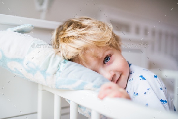 A toddler boy standing in a cot in the bedroom at home. - Stock Photo - Images