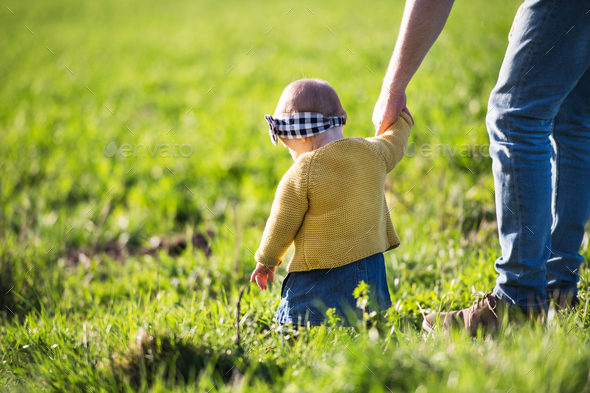 A father with his toddler daughter outside in spring nature. - Stock Photo - Images