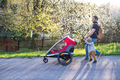 A father with toddler son pushing a jogging stroller outside in spring nature. - PhotoDune Item for Sale
