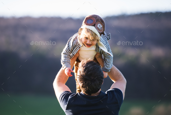 A father lifting his toddler son in the air outside in spring nature. - Stock Photo - Images
