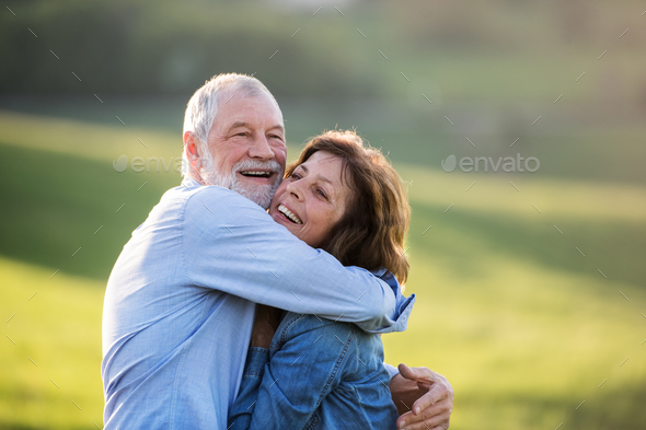 Senior couple hugging outside in spring nature. - Stock Photo - Images