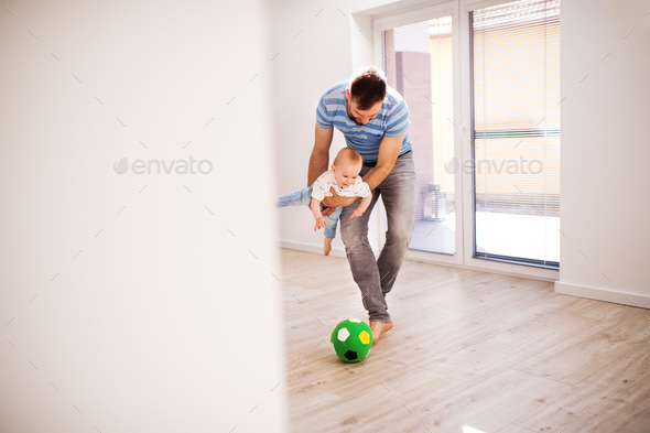 Young father with a baby son at home playing with a ball. - Stock Photo - Images
