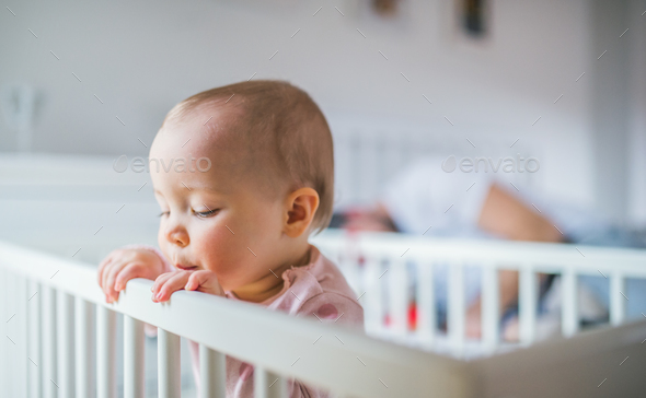 A toddler girl standing in a cot in the bedroom at home. - Stock Photo - Images