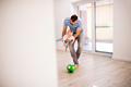 Young father with a baby son at home playing with a ball. - PhotoDune Item for Sale