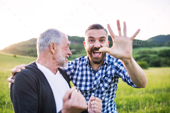 An adult hipster son with senior father on a walk in nature at sunset. - Stock Photo - Images