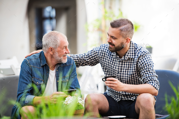 An adult hipster son and senior father with a cup of coffee in an outdoor cafe. - Stock Photo - Images