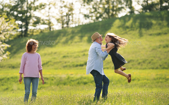 Senior couple with granddaughter outside in spring nature, having fun. - Stock Photo - Images