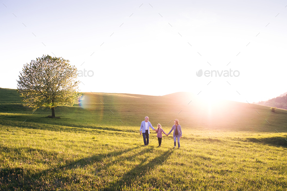 Senior couple with granddaughter outside in spring nature. - Stock Photo - Images