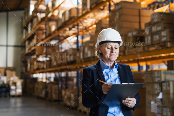 Senior woman warehouse manager or supervisor with white helmet and clipboard. - Stock Photo - Images
