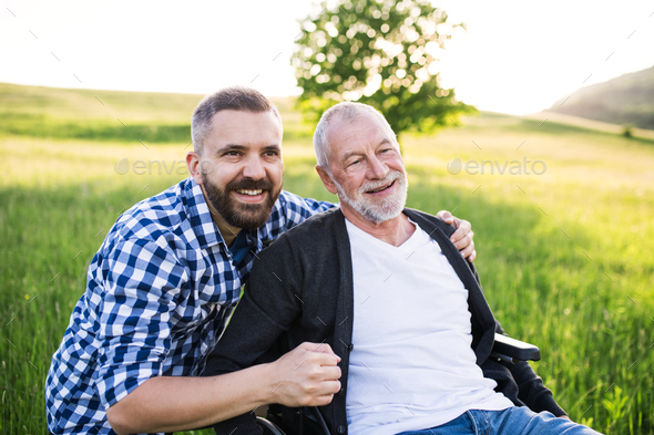 An adult hipster son with senior father in wheelchair on a walk in nature at sunset, laughing. - Stock Photo - Images
