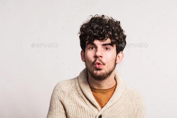 Portrait of a young man in woollen cardigan in a studio. Copy space. - Stock Photo - Images