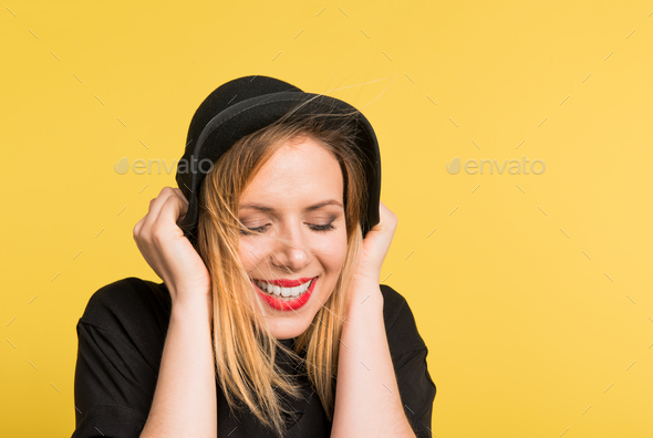 Portrait of a young beautiful woman with black hat in studio on a yellow background. - Stock Photo - Images