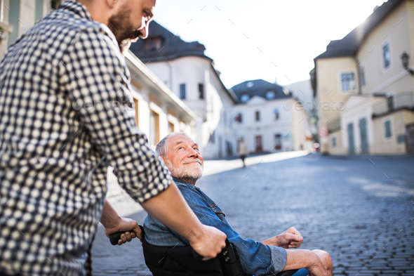 An adult son with senior father in wheelchair on a walk in town. - Stock Photo - Images