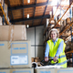 A senior woman warehouse worker pulling a pallet truck with boxes. - PhotoDune Item for Sale