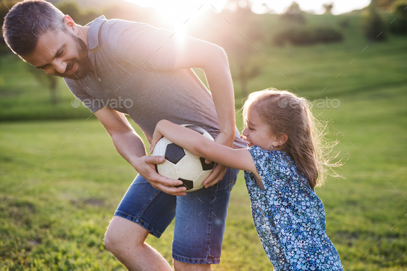 Father with a small daughter playing with a ball in spring nature. - Stock Photo - Images