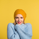 Portrait of a young beautiful woman with a woolen hat in studio on a yellow background. - PhotoDune Item for Sale