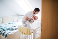 Father putting a sleeping toddler girl into cot at home. - PhotoDune Item for Sale